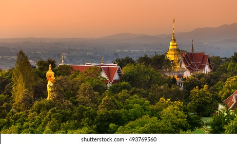 Scenic giant photo Buddha statue in sunset time in famous Thailand Temple Wat Phra That Doi Saket Temple on background green tropical trees and mountains in fog on horizon / Asia, Thailand, Chiang mai