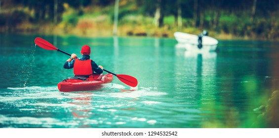 Scenic Glacial Lake Kayaking. Caucasian Sportsman in the Kayak on the Turquoise Water. Panoramic Photo.