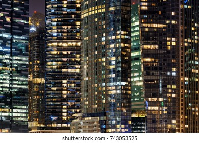Scenic glowing windows of skyscrapers at evening. View of modern office high-rise buildings in Singapore. Beautiful night cityscape.