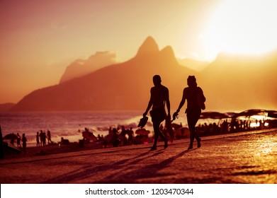 Scenic golden sunset view of Ipanema Beach with shadow silhouettes walking on the Arpoador boardwalk in Rio de Janeiro, Brazil