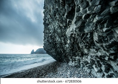 Scenic graphite rock at the seashore in cloudy weather