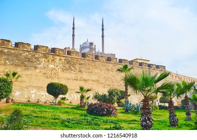 The scenic green garden with palms, trimmed trees and flower beds in front of the medieval wall of Saladin Citadel, hiding the scenic Alabaster Mosque with tall minarets, Cairo, Egypt.