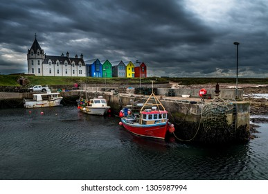 Scenic Harbor With Fishing Boats And Colorful Apartment Houses At John o'Groats In Scotland