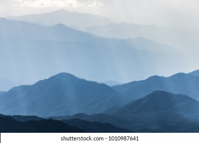 Scenic hazy blue mountains range covered by soft fog touching sunlight from cloudy sky.