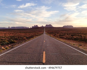 The scenic highway of U.S. Route 163 in Utah leading south to Arizona, through the red rocks of Monument Valley, in white cloud and blue sky on evening sunshine  in horizontal view.