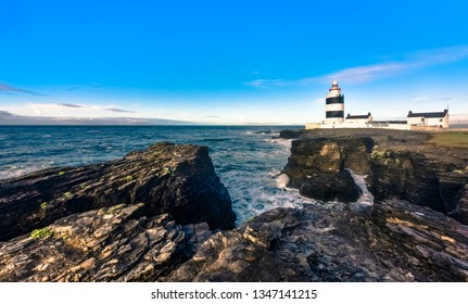 Scenic Hook Lighthouse on rugged cliffs with blue sky, Country Wexford, Ireland