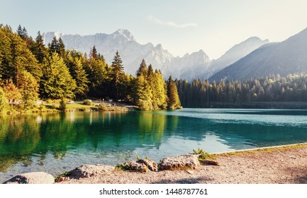 Scenic image of Fairytale lake Fusine during sunset. Picturesque landscape with lake, forest and majestic mount. Wonderful Autumn landscape. Picturesque view of nature. Amazing natural Background