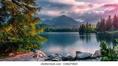 Scenic image of fairy-tale Landscape with colorful overcast sky under sunlit, over the Mountain Lake. Megical Natural Background. Amazing lake in sunset. Creative image. Strbske Pleso. Slovakia. Tatra