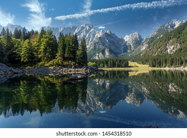 Scenic image of fairy-tale Mountain lake under sunlit. Amazing Nature Landscape. Wonderful sunny morning. Beautiful scenery of the majestic Fusine lakeside in Julian Alps. Perfect natural background