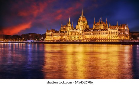 Scenic image of Hungarian parliament with reflections, Budapest with colorful dramatic sky during sunset. Fantastic view on Budapest sityscape. wonderful picturesque Scene. Popular Travel destinations