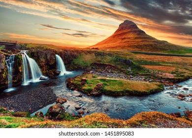 Scenic image of Iceland. The Kirkjufell volcano the coast of Snaefellsnes peninsula under bright sunlight during sunset. Majestic Kirkjufell (Church mountain) the most famous icelandic landmark