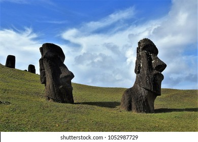 Scenic Image  of Two Moai Heads on Green Grass against Blue Sky with White Clouds at Rano Raraku, Rapa Nui (Easter Island)