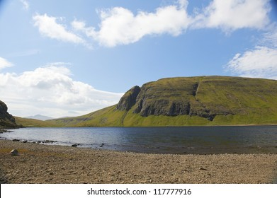 Scenic lake in the Faroe Islands on a summerday with blue sky and clouds