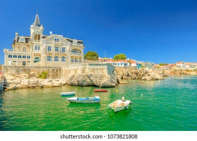 Scenic landscape of abandoned Palace Seixas and boats on the waterfront of Cascais, Lisbon Coast in Portugal. Praia da Rainha on the distance. Turquoise sea in summertime. Copy space with blue sky.