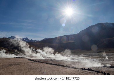 Scenic landscape of Atacama desert, Chile: Bright sun rise above El Tatio geyser field with many geysers, hot springs, and associated sinter deposits located in the Andes Mountain range