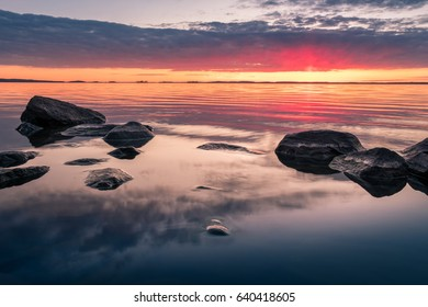 Scenic landscape with beautiful sunset and lake at spring evening in national park in Finland