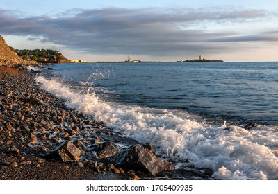 Scenic landscape of Black Sea coast by Bolshoy Utrish village, Anapa, Russia. Wave splashing on pebble beach at sunset