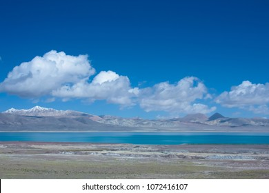 scenic landscape in cold shades with chilled highland lake, permafrost, bright blue sky with cumulus clouds over a distant undulating mountain range, Tibet, wide angle shot