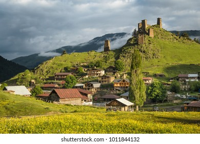 Scenic landscape of early summer morning in the depths of the Caucasus mountains. Sun just came out and illuminates ancient ruins of Tushetian defensive  towers. Village Omalo.