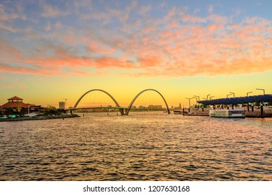 Scenic landscape of Elizabeth Quay Bridge on Swan River in Elizabeth Quay marina. The arched bridge is a new tourist attraction in Perth, Western Australia. Sky with red clouds of sunset.