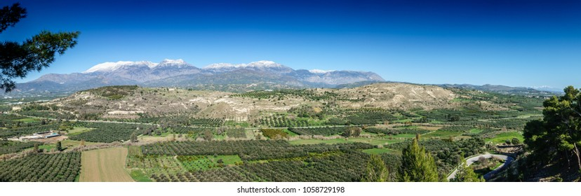 Scenic landscape with farms and mountains in background, Greece
