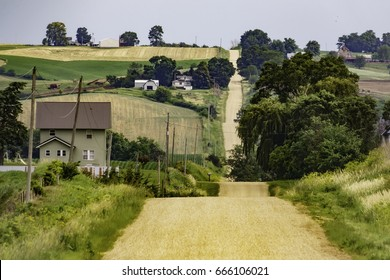 Scenic landscape with gravel road dipping across hilly farmland early in summer, northern Iowa, USA, for rural and regional themes