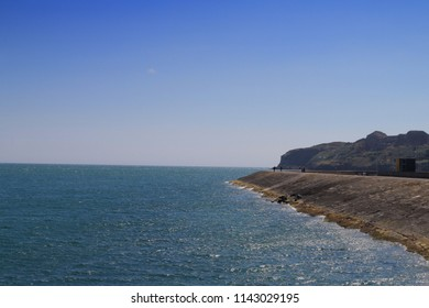 A scenic landscape in Howth, Dublin, Ireland, the east pier on a beautiful sunny day. day with the Hill of Howth swathes of blue sky and blue water.
