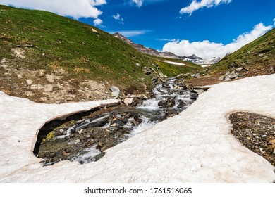Scenic landscape of italian mountains. Meadow, nature, little waterfall and a beautiful cloudy sky.