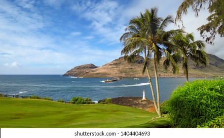 Scenic landscape of Kukii Point Lighthouse with palm trees, blue sea and sky, green golf course and mountains in the background, Kalapaki, Kauai, Hawaii, USA