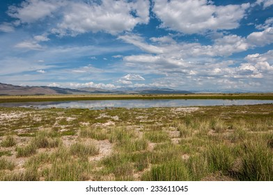 Scenic landscape with lake in steppe on a background of mountains, blue sky and clouds