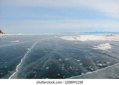 scenic landscape with mountain lake on a winter lovely day; thick dark blue ice with frozen bubbles and inner cracks; distant rocky shore; delicate shade of morning sky in the frosty haze