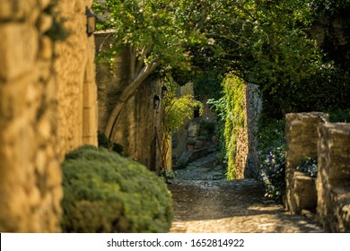 Scenic landscape of old narrow street in one of the most beautiful villages of France Lacoste, Luberon, Vaucluse, Provence with traditional old houses and green trees in summer sunny day. Travel
