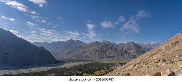 Scenic landscape panorama on Wakhan Corridor overlooking Panj river valley and snow-capped Hindu Kuch mountain range in Afghanistan in background, Gorno-Badakshan, Tajikistan - Shutterstock ID 2018603987