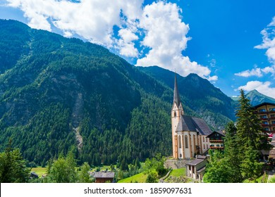 A scenic landscape photo of the Austrian municipality of Heiligenblut with St. Vincent Church in front of the Hohe Tauern mountains. Cetral Alps mountains in the background.
