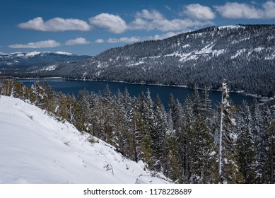 A scenic landscape photo of Donner Lake, trees and mountains in the winter snow,  in the Sierra Mountains, in California.
