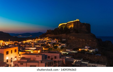 Scenic landscape photo of night Lindos town and castle on Rhodes island, Dodecanese, Greece. Panorama with bright lights, mountains and sea. Famous tourist destination in South Europe