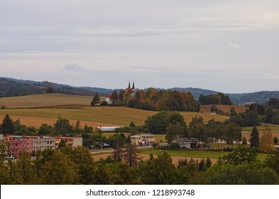Scenic landscape of typical small town and nature around it in. Residential buildings, gas station, fields and hills with many trees.  Telc, Southern Moravia, Czech Republic.