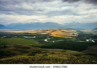 Scenic landscape with vast plateau with mountain river and forest in sunlight on background of snowy mountain ridge under cloudy sky. Green mountain valley in sunshine and mountain range on horizon.