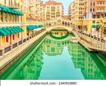 Scenic landscape of Venice at Qanat Quartier in the Pearl-Qatar, Persian Gulf, Middle East. Panoramic view of Venetian bridge reflecting on canals of picturesque and luxurious district of Doha, Qatar.