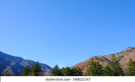 Scenic landscape view of nature forest with  mountain range trees and clear blue sky background in fall season of kamikochi, in Hotaka Ranges, Kamikochi, Japan.