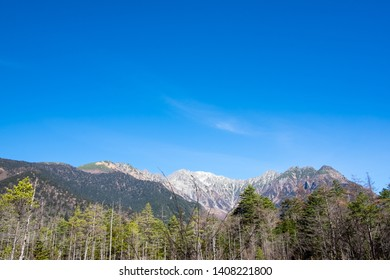 Scenic landscape view of nature forest with white snow mountain green trees and clear blue sky background in fall season of kamikochi, in Hotaka Ranges, Kamikochi, Japan.