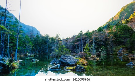 Scenic landscape view of nature with mountain trees and water pond in fall season of kamikochi, in Hotaka Ranges, Kamikochi, Japan.