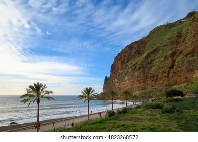 Scenic landscape view of promenade with palm trees, ocean and mountain cliff in late afternoon light, Madalena do Mar, Madeira, Portugal, Europe