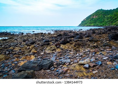 Scenic landscape view of rock stone on the beach with water sea tropical mountain and sky background.