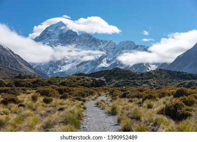 Scenic landscape view of snowcapped Mount Cook peaking through clouds at Hooker Valley, Aoraki/Mount Cook National Park, South Island of New Zealand.Tourist popular hiking attraction/destination.