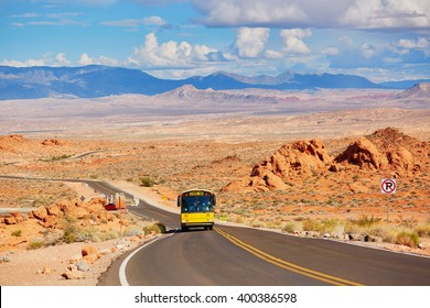 Scenic landscape with winding road and yellow school bus during field trip in Valley of the Fire  park in Nevada, USA