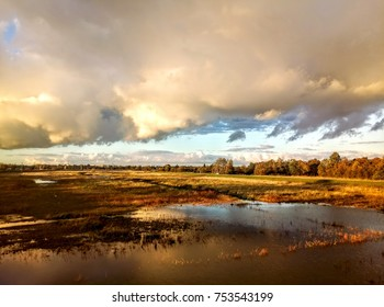 Scenic lanscape of amazing clouds above flooded fields and meadows. Waterscape autumn fall view. Beautiful scape with plants and river, nature wonder. Amazing sky and cloud formations. Seasons.
