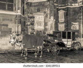 Scenic monochrome vintage street photo of a horse coach taken on the backside of St. Stephen's cathedral, Vienna, Austria