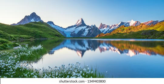 Scenic morning reflection view on Bernese range above Bachalpsee lake. Popular tourist attraction. Location place Swiss alps, Grindelwald valley, Europe.