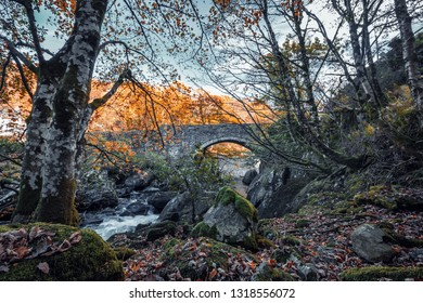 Scenic mountain creek at autumn with old bridge in background. Snowdonia National Park in North Wales